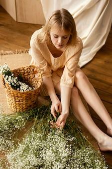 Alto angolo di donna con fiori primaverili