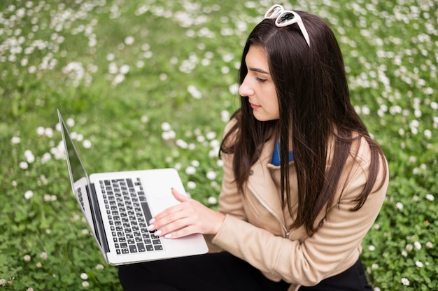 High angle of woman working on laptop outdoors