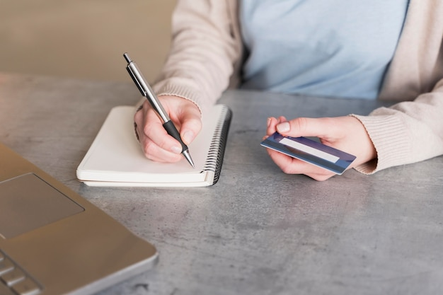 High angle of woman writing down on notebook while holding credit card