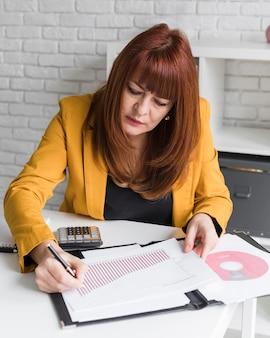 Женщина высокого угла, пишущая на бумажном листе