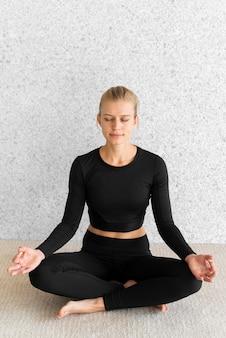 Donna di alto angolo nella posa di yoga