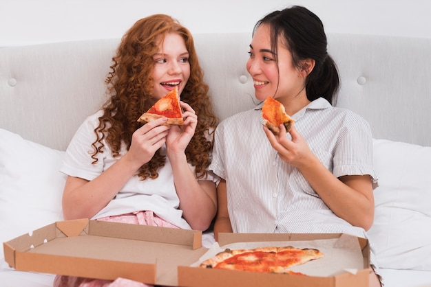 High angle women in bed eating pizza