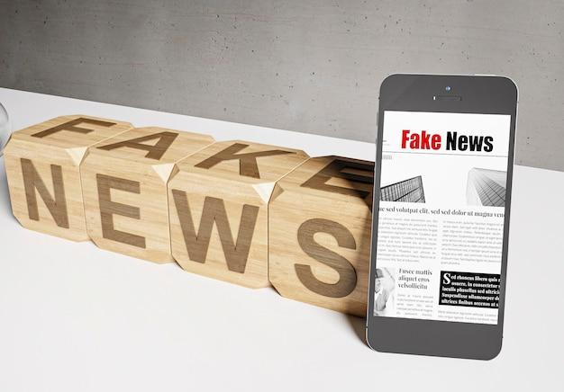 Angolo alto di cubi di legno con notizie false e smartphone