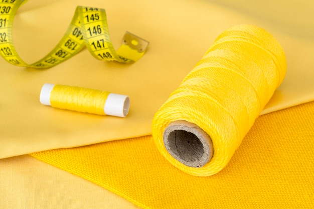 High angle of yellow thread rolls and measuring tape