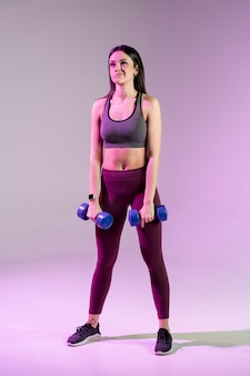 High angle young female exercising with weights