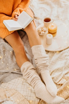 Молодая женщина под высоким углом наслаждается зимними каникулами с чашкой чая