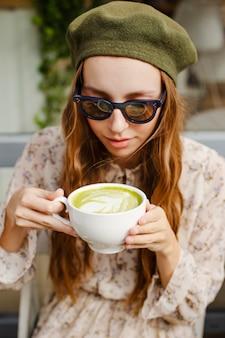 Высокий угол молодая женщина, держащая чашку латте матча