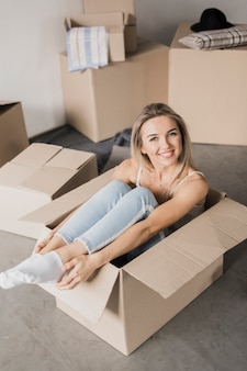 High angle young woman sitting in a box