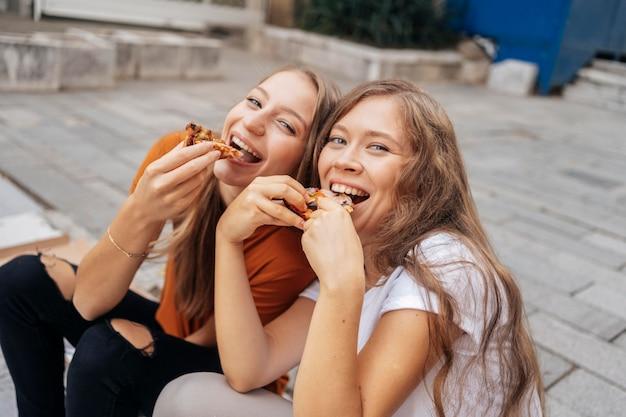 Giovani donne di alto angolo che mangiano pizza insieme