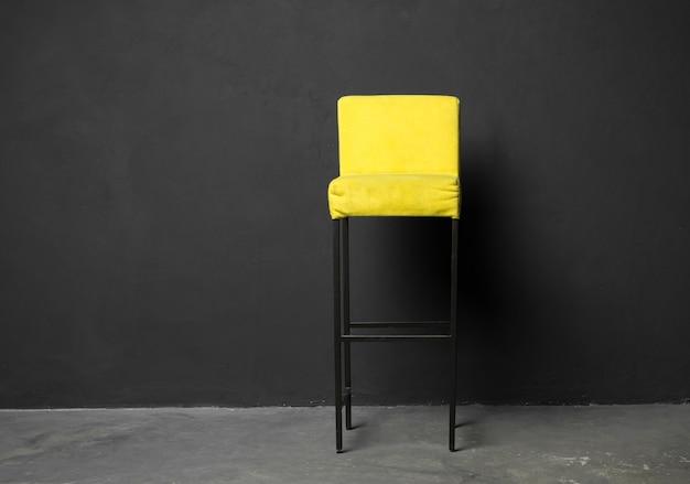 Высокий барный стул у темно-серой стены. стильное кресло в стиле лофт, в классическом интерьере