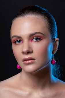 High beauty photo of a lovely young girl with wonderful professional makeup, round pink earrings, with long brown hair. posing over black background. closeup. studio shot. portrait