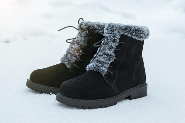 첫 눈에 높은 검은색 세련된 여성용 부츠. 아름답고 실용적인 여성용 겨울 신발.