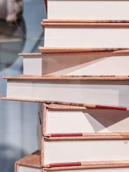 Стопка высоких книг, изолированные на размытом фоне. перед группой сложенных книг. старые книги на полке в библиотеке