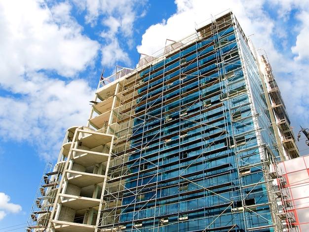 푸른 하늘 배경에 유리와 콘크리트로 된 높은 건물. 공사중