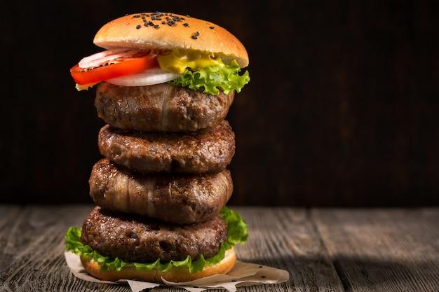 暗いテーブルの上の高いハンバーガー