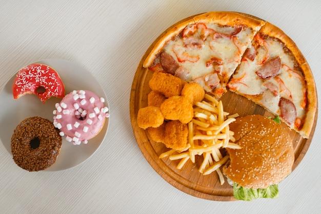 テーブルの上の高カロリー食品、上面図、誰も。ピザとハンバーガー、ドーナツ、フライドポテトとチキンナゲット。ジャンクファーストフード