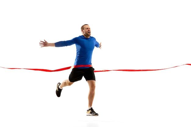 高い。白人のプロのジョガー、白い壁に隔離されたランナートレーニング。筋肉質でスポーティーな男、感情的。アクション、モーション、若さ、健康的なライフスタイルの概念。広告のコピースペース。