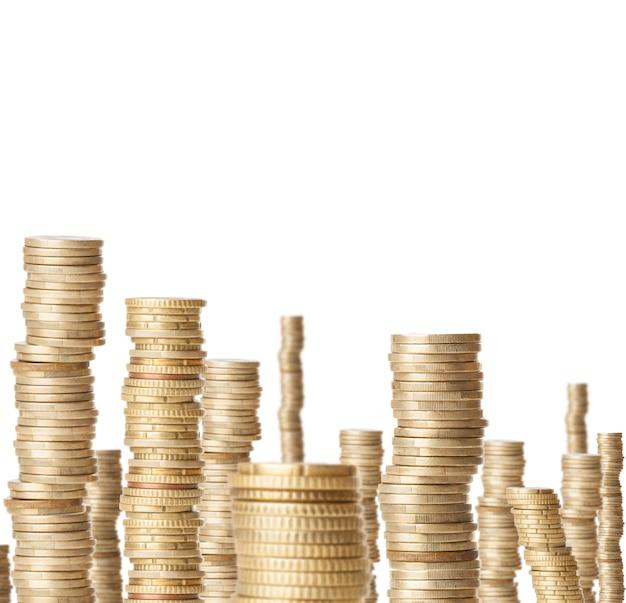 Alte torri di monete che rappresentano la ricchezza isolati