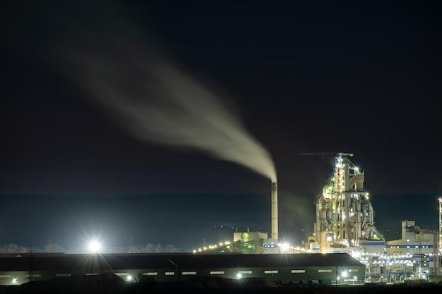 타워 크레인과 밤에 흡연 굴뚝 시멘트 공장의 높은 콘크리트 구조.