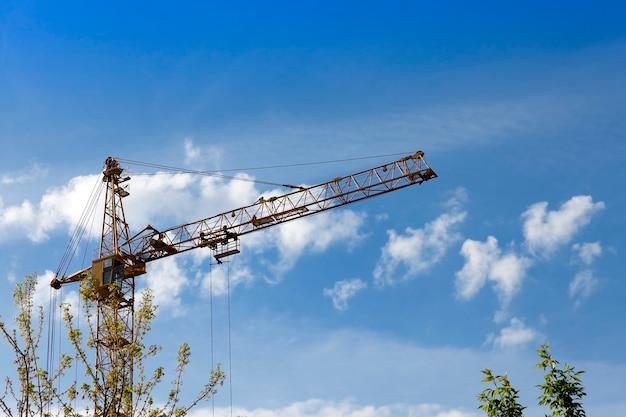 Высокие строительные краны на фоне голубого неба.