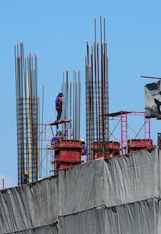 コンクリートセメント金属材料を使用して作業している高建設現場と労働者。