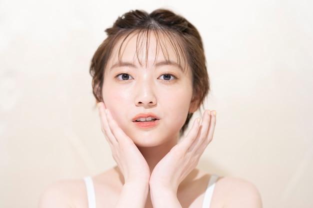 メイクアップの若いアジアの女性とのハイコントラスト照明