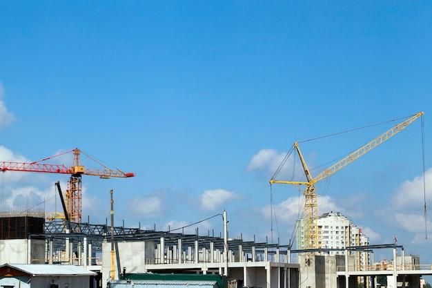 Высокие краны на строительстве нового торгового центра. на заднем плане голубое небо с облаками