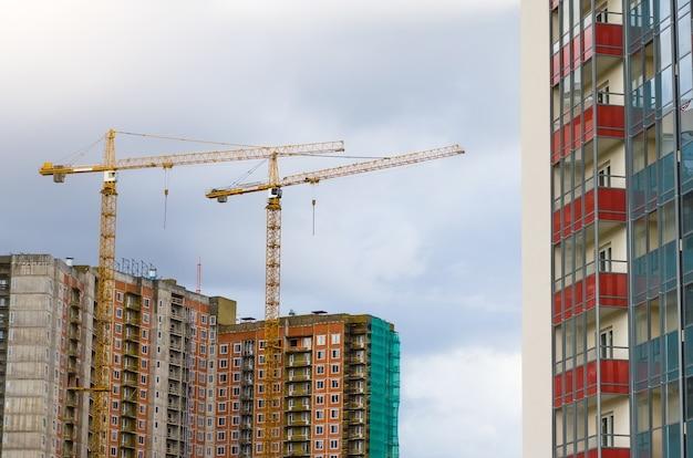 Высокие краны на строительстве жилых домов.