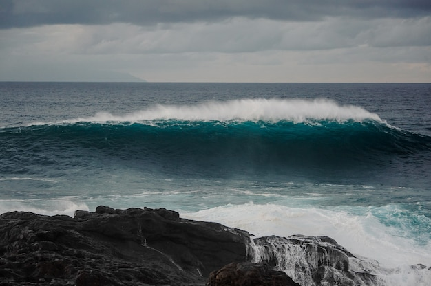 Высокая глубокая лазурная морская волна с пеной и черная скала под пасмурным серым небом в штормовой день