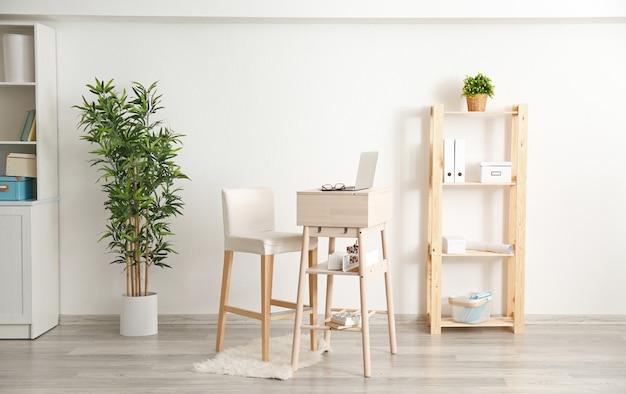 방에 노트북과 의자가 있는 높은 책상