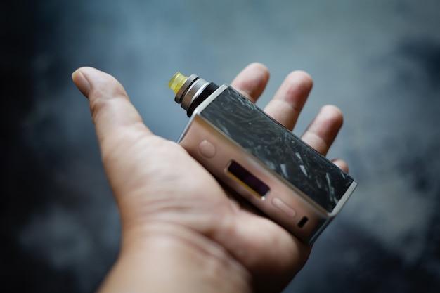어두운 회색 질감 배경, 기화기 장비, 선택적 초점에 재구축 가능한 물방울 분무기와 울템 드립 팁이 있는 투명 수지 조절 상자 모드의 고급 검정 탄소 섬유