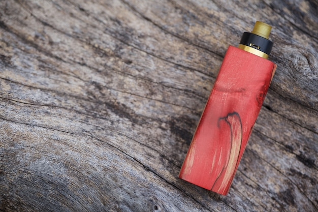 High end red natural stabilized wood regulated box mods with rebuildable dripping atomizer on natural timber wood texture , vaporizer equipment, selective focus