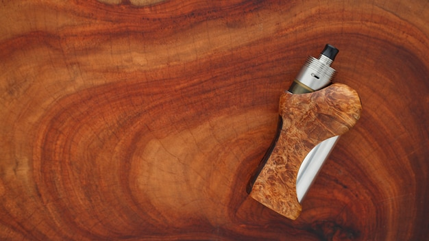 High end titanium genesis atomizer with stabilized natural black ash wood regulated box mods on natural wood texture background, vaping device, selective focus