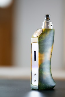 High end yellow green stabilized poplar burl wood box mods with rebuildable dripping atomizer and drip tip, vaping device, vape gear, vaporizer equipment, selective focus