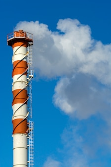 High factory chimney with smoke against the sky