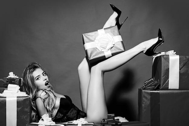 하이 패션. 빨간색 배경 위에 절연 선물 상자에 흥분된 귀여운 소녀. 어머니의 날. 긴 섹시