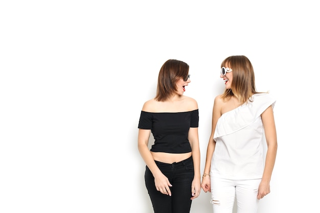 High-fashion. glamorous stylish young women model with red lips in a black and white bright hipster clothes and sunglasses. they laugh, rejoice, rage, indulge
