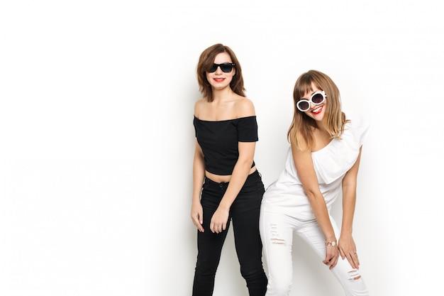 ハイファッション。黒と白の明るい流行に敏感な服とサングラスで赤い唇と華やかなスタイリッシュな若い女性モデル。