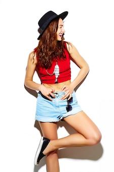 ファッション性の高い外観。面白いグラマースタイリッシュなセクシーな笑みを浮かべて美しい若い女性モデルのキャップで夏の明るい流行に敏感な布