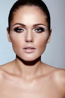 Ritratto del primo piano di look.glamor di alta moda di bello modello caucasico della giovane donna del brunette con trucco luminoso con pelle pulita perfetta