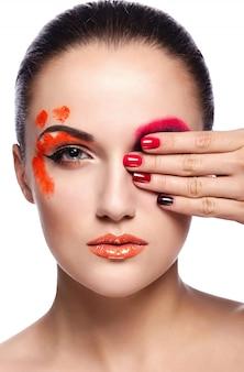 Ritratto del primo piano di look.glamor di alta moda di bello modello sexy della giovane donna castana con le labbra arancio e pelle pulita perfetta con le unghie variopinte