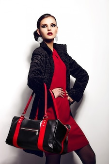 High fashion look.glamor closeup portrait of beautiful sexy stylish brunette caucasian young woman model in red dress with black bag bright makeup, with red lips,  with perfect clean skin in studio
