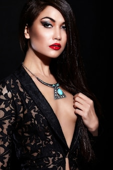 High fashion look.glamor closeup portrait of beautiful sexy stylish brunette caucasian young woman model with bright makeup, with red lips,  with perfect clean skin with jewelery in black cloth
