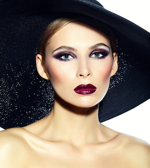 High fashion look.glamor closeup portrait of beautiful sexy stylish  young woman model with bright makeup with red lips with perfect clean skin in casual cloth in hat