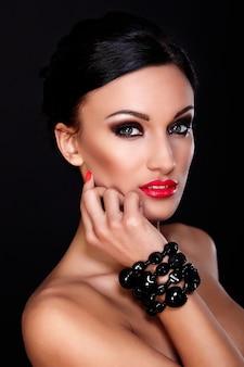 赤い唇、明るいメイク、黒に分離された完璧なきれいな肌と美しいセクシーな白人若い女性モデルのファッション性の高いlook.glamorのクローズアップの肖像画