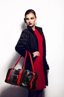 스튜디오에서 완벽한 깨끗한 피부와 빨간 입술 검은 가방 밝은 화장과 빨간 드레스에 아름 다운 섹시 세련된 갈색 머리 백인 젊은 여자 모델의 높은 패션 look.glamor 근접 촬영 초상화