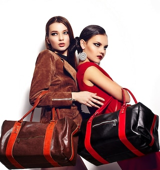 High fashion look.glamor closeup portrait of  two beautiful sexy stylish brunettes caucasian young women models with bright makeup, with red lips,  with perfect clean skin in studio