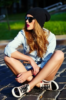High fashion look.glamor lifestyle blond woman girl  model in casual jeans shorts cloth sitting  outdoors in the street in black cap  in glasses