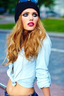 Высокая мода look.glamor образ жизни белокурая женщина девушка модель в повседневных джинсовых шортах ткани на улице на улице в черной кепке в очках