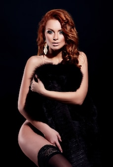 High fashion look.glamor portrait of beautiful sexy redhead stylish nude caucasian young woman model with bright makeup, with perfect clean in lingerie in fur coat